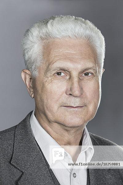 Nahaufnahme eines selbstbewussten älteren Mannes über grauem Hintergrund