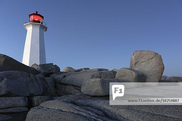 Flachwinkelansicht des Leuchtturms auf Felslandschaft gegen klaren blauen Himmel