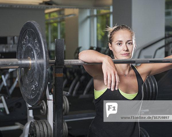 Porträt einer Frau  die sich in der Turnhalle auf die Langhantel stützt.