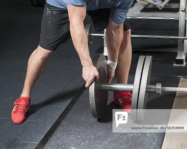 Niedriger Abschnitt des Mannes  der Gewichte auf Langhantel hinzufügt.