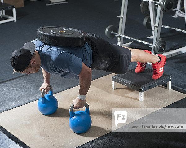 Volle Länge des jungen Mannes  der in der Turnhalle trainiert.