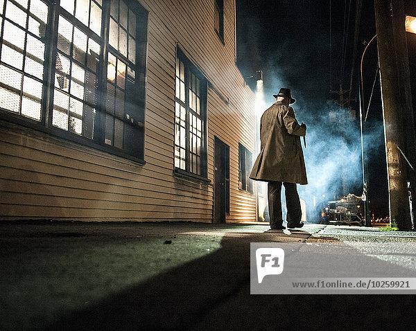 Rückansicht des Mannes  der nachts außerhalb des Gebäudes geht.