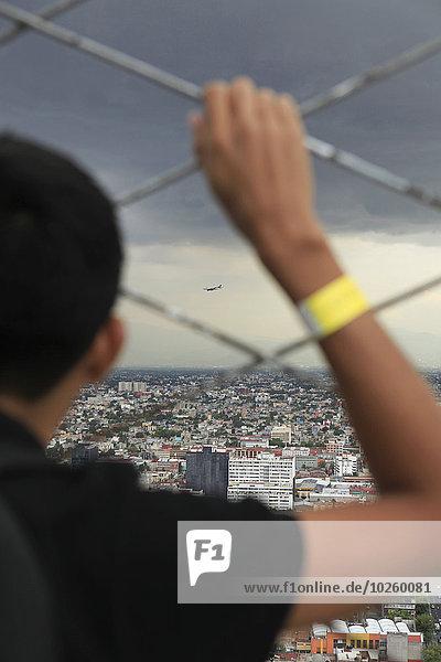 Abgeschnittenes Bild von Jungen  die das Stadtbild durch einen Kettengliedzaun beobachten.