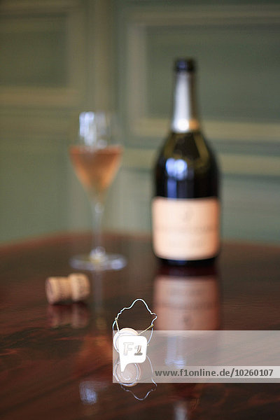 Weinflasche und Glas auf Holztisch