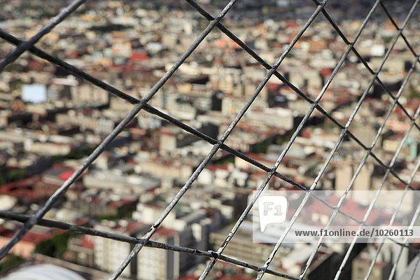 Stadtbild durch einen Kettengitterzaun gesehen
