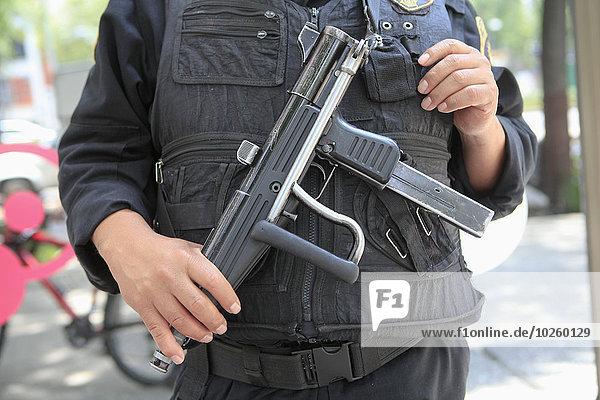 Mittelteil des Sicherheitsoffiziers mit Waffe auf der Straße