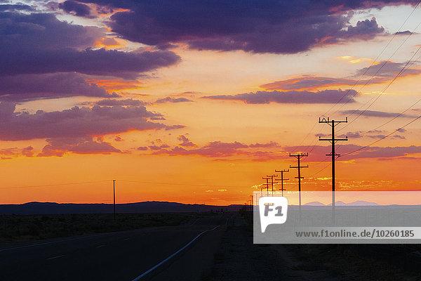 Landstraße und Silhouettenfeld gegen bewölkten Himmel bei Sonnenuntergang