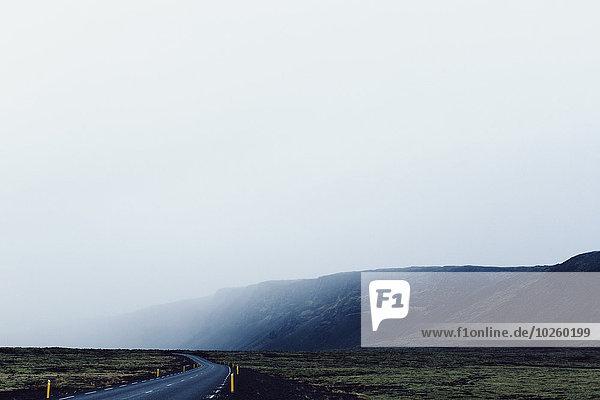 Landstraße am Berg vorbei bei Nebelwetter gegen klaren Himmel