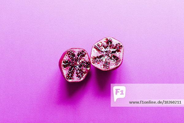 Granatapfelschnitt in der Mitte auf rosa Hintergrund
