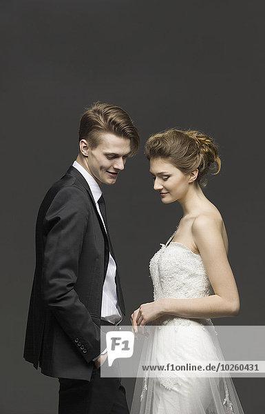 Seitenansicht des frisch verheirateten Paares über grauem Hintergrund