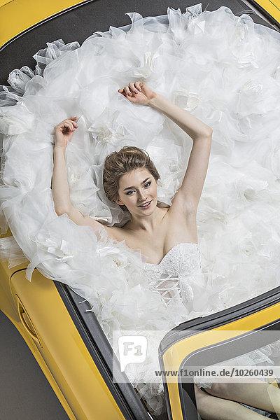 Hochwinkelansicht der jungen Braut im Brautkleid sitzend im Cabriolet