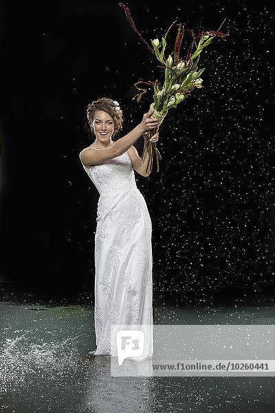 Ganzflächiges Porträt der lächelnden jungen Braut mit Blumenstrauß im Wasser gegen schwarze Bären.