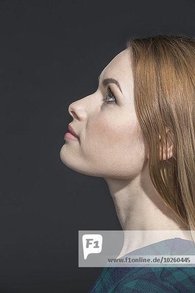 Seitenansicht der nachdenklichen jungen Frau  die über den grauen Hintergrund schaut