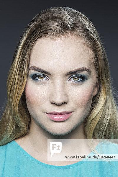 Porträt einer schönen jungen Frau mit blonden Haaren auf grauem Hintergrund