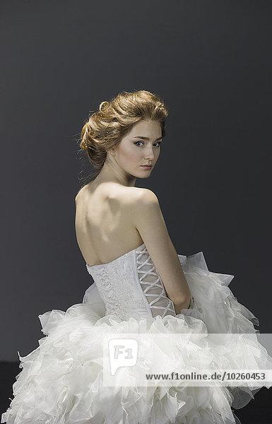 Portrait der jungen Braut im Brautkleid über farbigem Hintergrund
