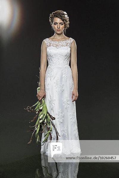 Porträt einer traurigen jungen Braut mit verwelktem Blumenstrauß im Wasser vor grauem Hintergrund