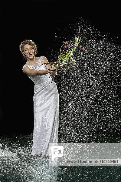 Aufgeregte junge Braut spritzt Wasser mit Blumenstrauß vor schwarzem Hintergrund