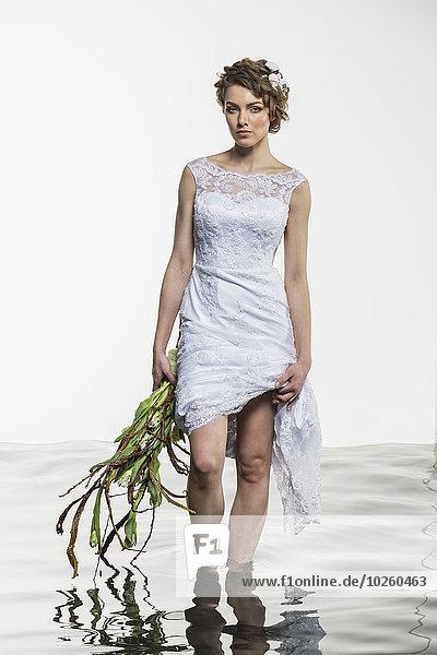 Porträt der jungen Braut mit Kleid und verwelktem Strauß im Wasser stehend auf weißem Rücken