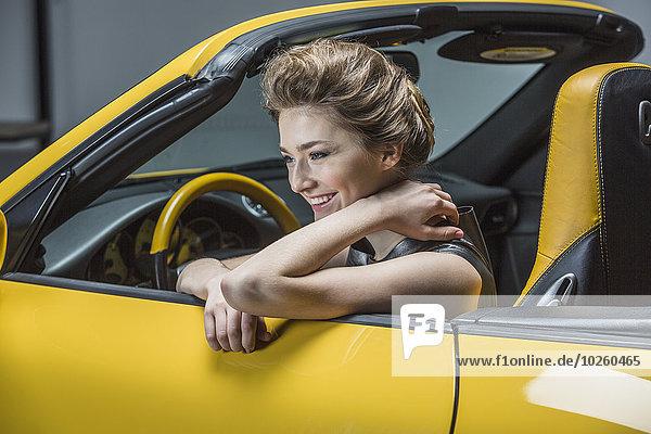 Glückliche Frau schaut weg  während sie im Cabrio sitzt.