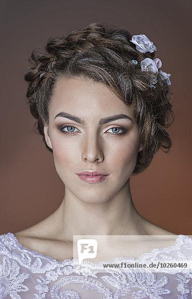 Nahaufnahme der schönen jungen Frau vor farbigem Hintergrund
