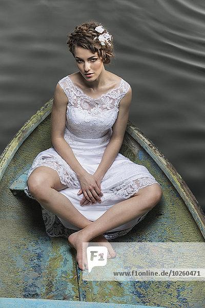 Hochwinkelporträt einer traurigen jungen Braut im Boot auf dem See