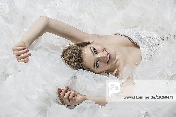 Porträt der lächelnden jungen Braut im Brautkleid liegend