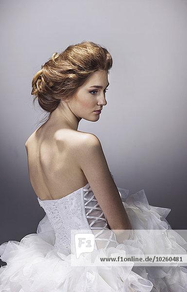 Traurige junge Braut im Brautkleid stehend vor grauem Hintergrund