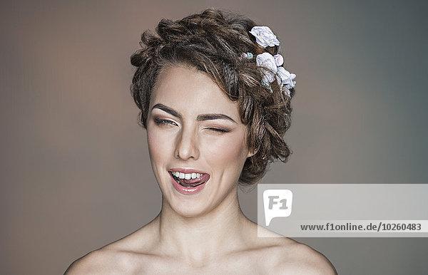 Porträt einer verspielten jungen Frau  die vor farbigem Hintergrund blinzelt.