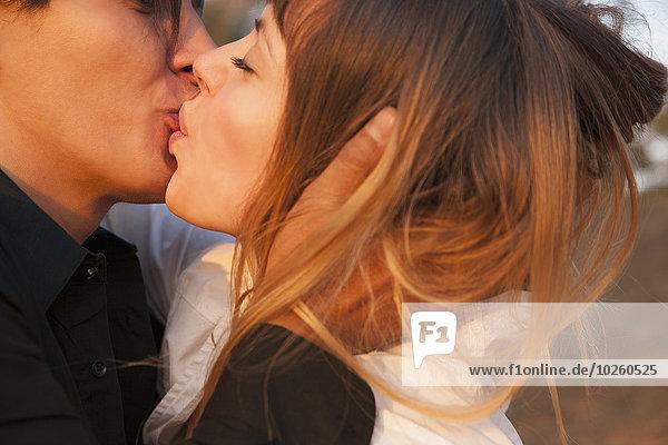 Seitenansicht des romantischen Paares beim Küssen im Freien