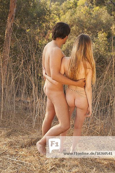 Rückansicht des nackten Paares  das in der Natur steht