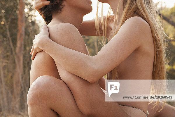 Seitenansicht des nackten Paares  das sich in der Natur liebt