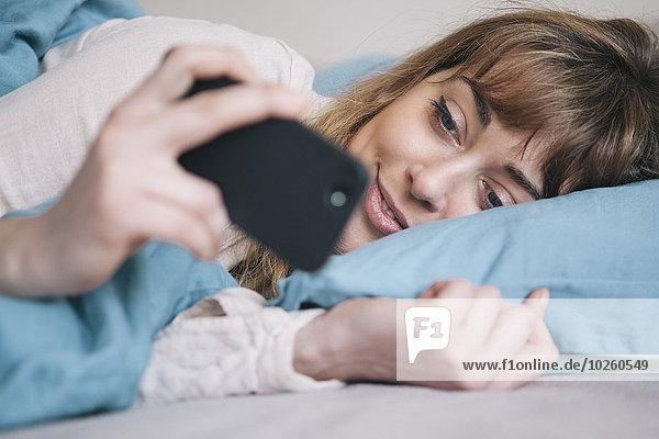 Junge Frau mit dem Handy im Bett entspannen