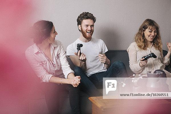 Aufgeregte junge Freunde beim Spielen von Videospielen zu Hause