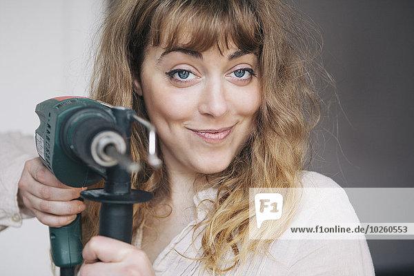 Porträt einer selbstbewussten jungen Frau mit Bohrmaschine zu Hause