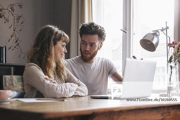 Junges Paar im Gespräch mit Laptop auf dem Tisch zu Hause