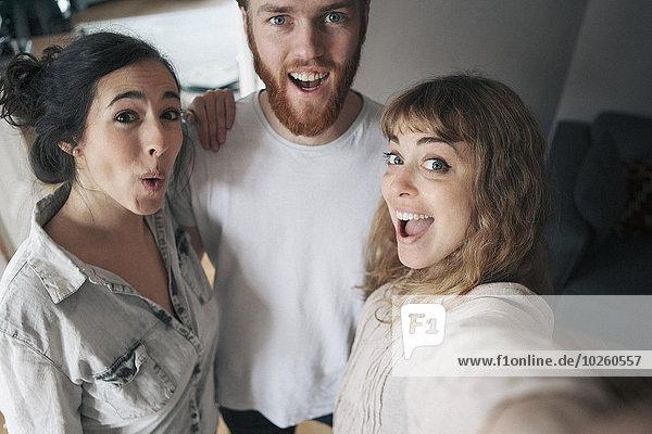 Porträt eines jungen Mannes mit Freundinnen  die Spaß zu Hause haben