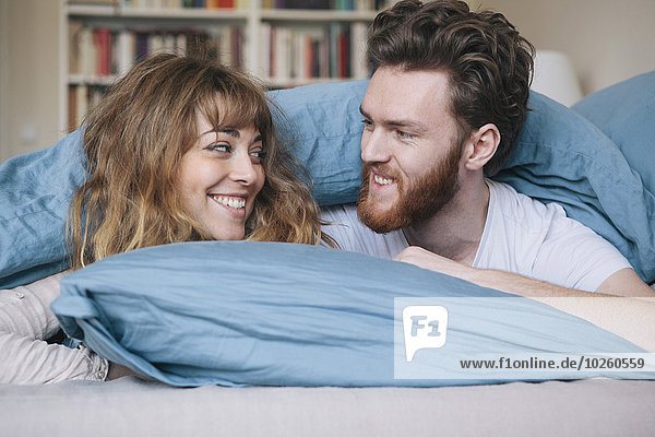 Liebende junge Paare sehen sich an  während sie im Bett liegen.