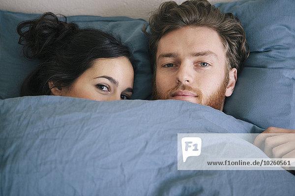 Porträt eines liebenden jungen Paares unter Bettdecke im Bett