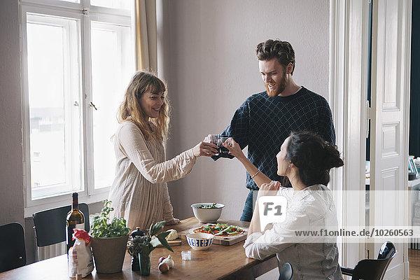 Junger Mann mit weiblichen Freunden beim Weintoasten zu Hause
