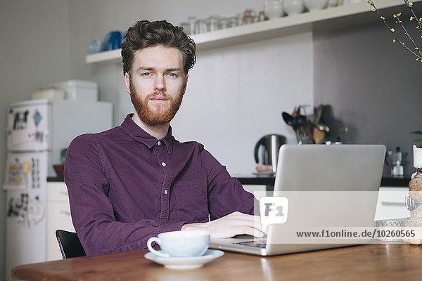 Porträt eines selbstbewussten jungen Mannes mit Laptop am Tisch in der Küche