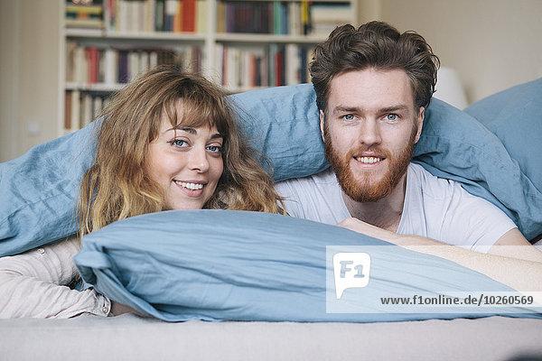 Porträt eines glücklichen jungen Paares im Bett liegend