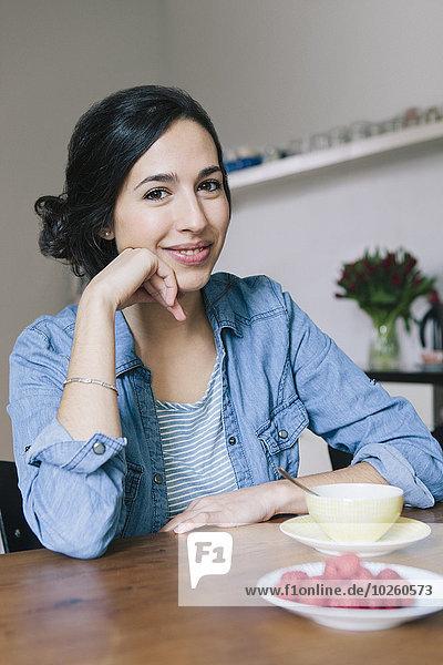 Porträt einer glücklichen jungen Frau  die am Tisch in der Küche sitzt.