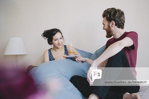 Porträt einer glücklichen jungen Frau  die einen Geburtstagskuchen mit Kerze hält  während sie neben einem Mann auf dem Bett sitzt.
