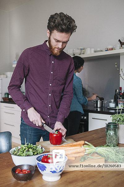 Junger Mann hackt rote Paprika am Küchentisch mit Frau im Hintergrund