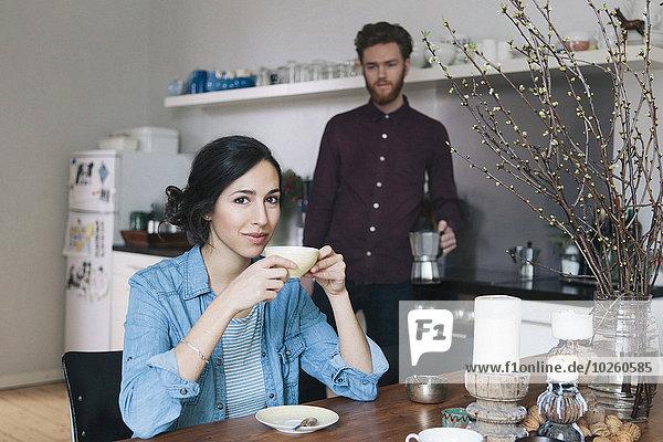 Porträt einer jungen Frau beim Kaffeetrinken am Küchentisch mit Mann im Hintergrund
