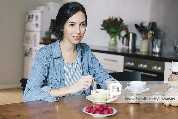 Porträt einer glücklichen jungen Frau beim Kaffeetrinken in der Küche