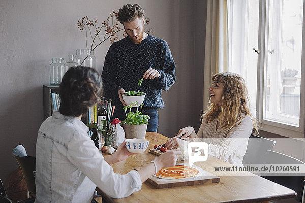 Junger Mann mit weiblichen Freunden  die bei Tisch Pizza machen