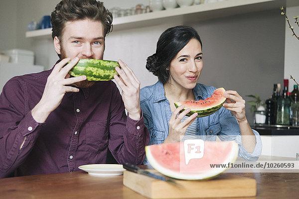 Porträt eines glücklichen jungen Paares beim Essen von Wassermelone am Küchentisch