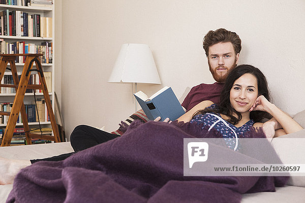 Porträt einer glücklichen jungen Frau mit einem Mann  der ein Buch im Bett hält.