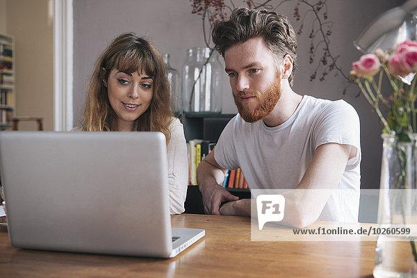 Junges Paar schaut auf den Laptop auf dem Tisch